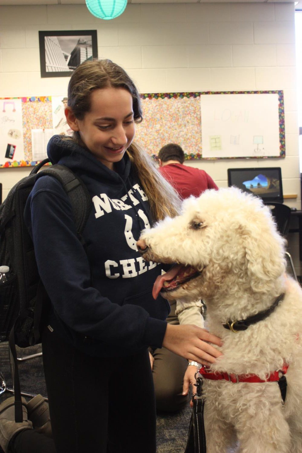 Senior Sami Gotskind pets a dog during North Time in puppy cubby last year.