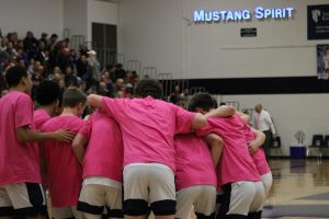 The Mustangs huddle up before the game starts.