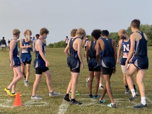 Boys on the Varsity team huddle up seconds before a race.