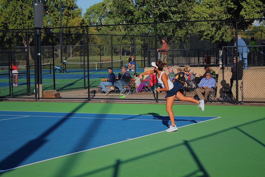 Joy Yan follows through her serve.