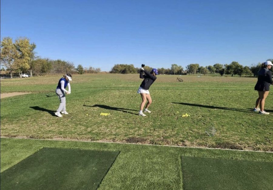 Carlie Kidwell and Olivia Still warmup for the tournament at the driving range. Photo provided by Olivia Still.